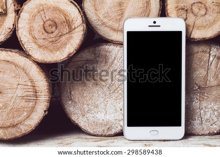 White mobile phone with a camera is on logs - stock photo