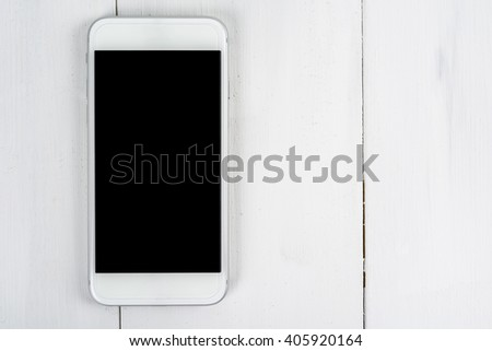 White Mobile Phone With Blank Screen On Wood Table - stock photo