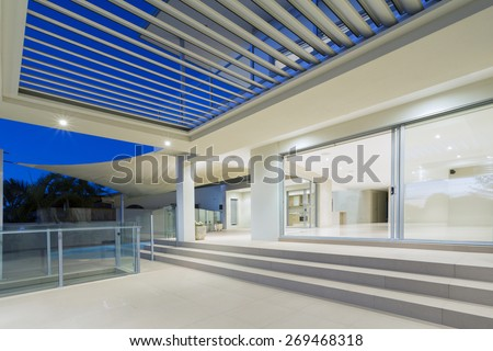 White modern luxurious mansion exterior with deck and swimming pool on the Gold Coast, Queensland Australia
