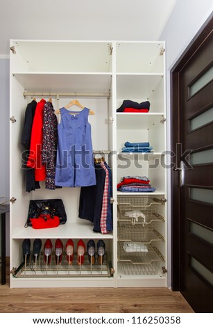 white modern wardrobe withfemale red and blue  closing - stock photo