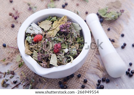 White mortar and pestle with dry herbal tea with blackberry and dog rose - stock photo