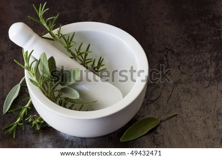 White mortar and pestle with fresh hers, including rosemary, oregano and sage, over marbled slate background.