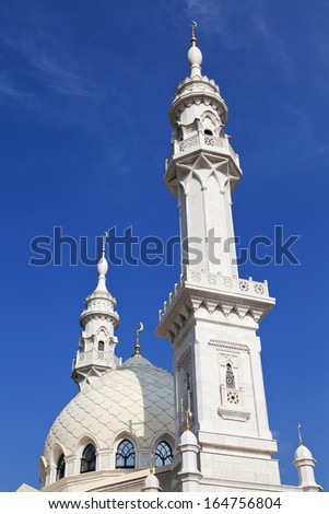 White mosque with high menarets against the blue sky
