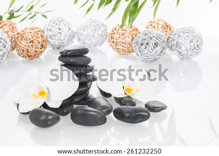 White Moth orchids, black zen stones with gold and silver twig balls over white background - stock photo