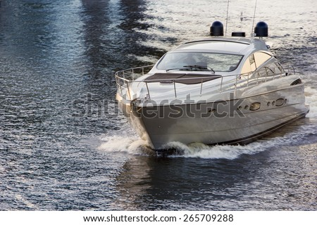 white motor boat on water at sunset - stock photo