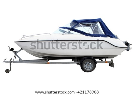 White motor boat with a blue awning loaded on a trailer for transportation. - stock photo