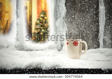 white mug and white snow on window sill  - stock photo