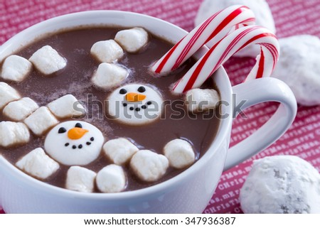 White mug filled with hot chocolate with snowman shaped marshmallows ...