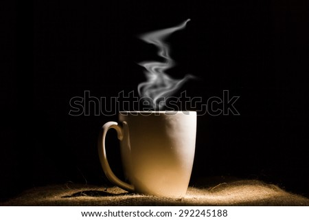 White mug of hot coffee or hot drink in dark. - stock photo