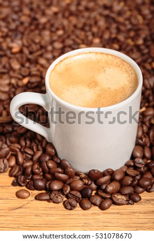 White Mug with Coffee over Dark Brown Coffee Beans.