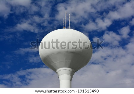 White Municipal Water Storage Tower and Cell Phone Signal Tower Against a Beautiful Blue Sky - stock photo