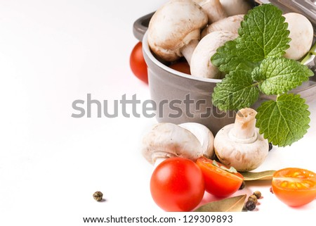 white mushrooms in pan, sliced cherry tomatoes, garlic and mint over white