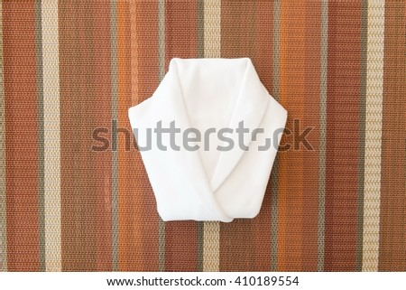 White napkin folded into a shirt on dinner table taken from top view - stock photo