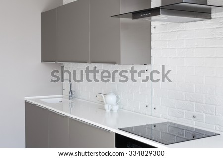 White new modern kitchen with counter top and exhaust hood - stock photo