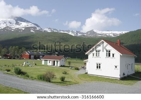 white Norwegian house on the background of snowy mountains - stock photo