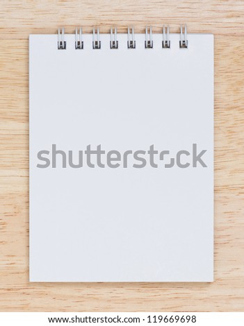 white note book isolated on wood  background