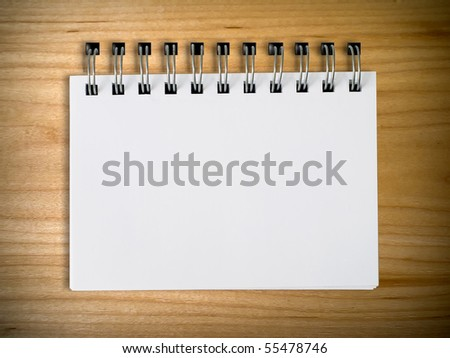 White note book on wood background