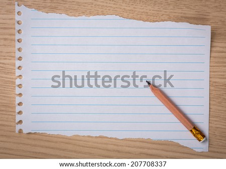 White note book paper with  pencil on a wooden desk