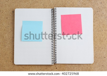White note paper bookmark with sticker note on book  pages. - stock photo