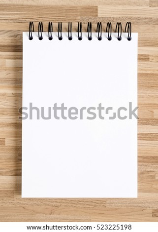 White notebook on wooden texture background.