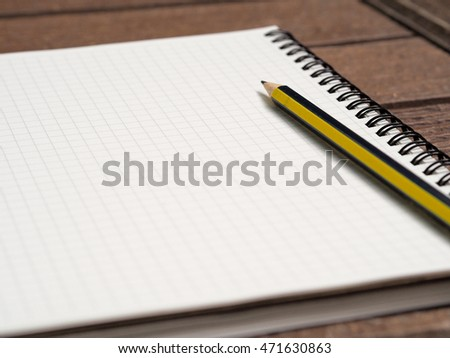 White notebook with one pencil on the garden floor, ready to write down any great idea on the note with normal pencil