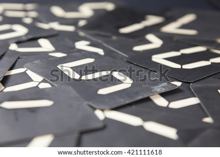 white numbers on black cardboard of a vintage clock mixed on a table, macro close-up