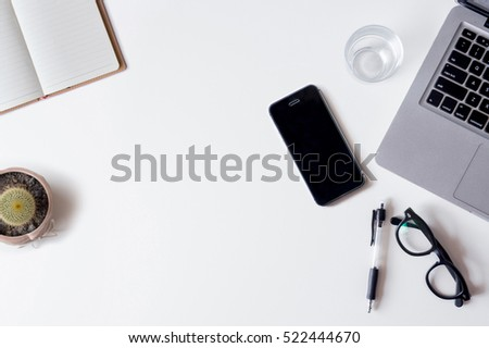 White office desk table with laptop, smartphone, notebook, and glass. Top view with copy space, flat lay.
