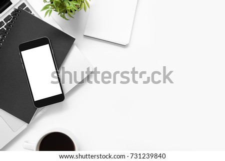 neat office supplies. white office desk table with smartphone blank screen and other supplies. top view neat supplies