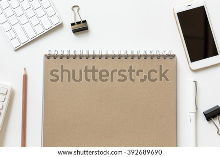 White office table with supplies. Brown notebook, mobile, keyboard, office supplies. Office modern desk project. - stock photo