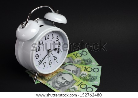 White old fashion alarm clock with Australian hundred dollar notes on black background for time and money concept.