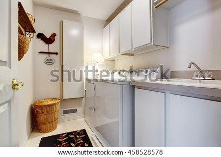 White old style laundry room interior with tile floor, washbasin cabinet and wicker basket in the corner.