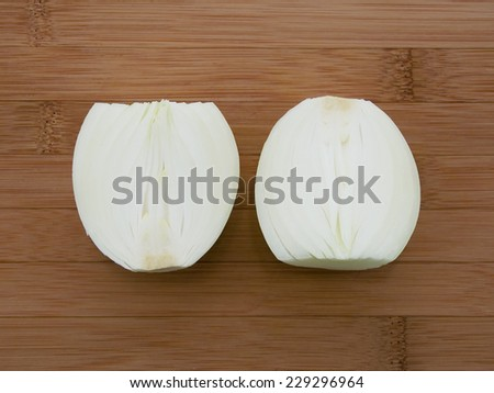 white onion sliced in half over cutting board - stock photo