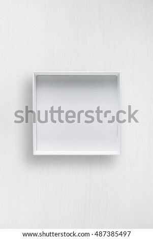 White open box on white table