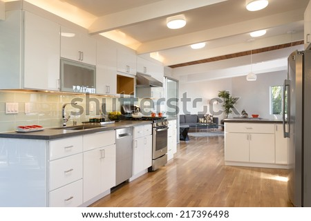 White open designer kitchen with fitting enthralling cabinets furniture and grey marble counter tops with breakfast bar and bar chairs. - stock photo