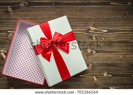 White open new year or Christmas gift box with red ribbon for holiday concept on brown wooden board. Top view with empty space for text and design.