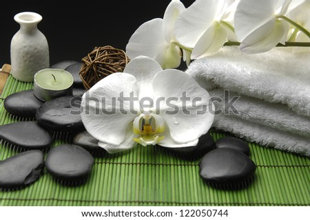 White Orchid and zen stones with towel and candle on mat