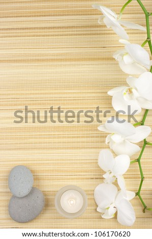white orchids, candles and stones on mat. - stock photo
