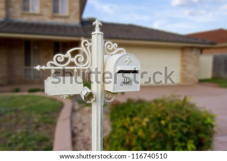 white ornamental Letter box with a facility to write house number and a newspaper holder in front of a beautiful house - stock photo