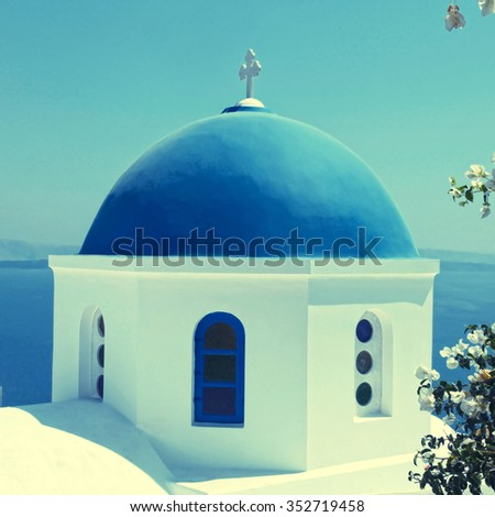 White orthodox church with blue dome with sea view in the village of Oia, Santorini island, Greece. Square toned image, instagram effect - stock photo