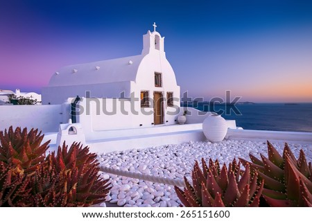 White othodox church in Oia on Santorini, Greece, during a sunset with red plants in front - stock photo