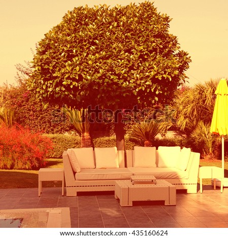 white outdoor furniture in the beautiful garden near the swimming pool for relax on summer resort. Vintage toned image - stock photo