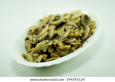 White oval plate filled with gold brown fried mushrooms. Isolated