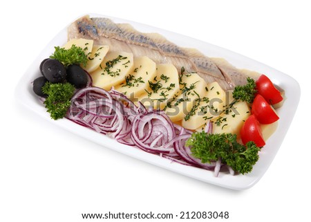 White oval plate with slices of pickled herring fillets, fresh onion rings, and boiled potatoes sprinkled with dill isolated on a white background. - stock photo