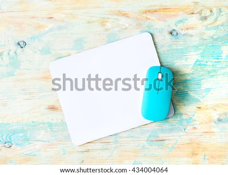 white pad with blue mouse on colorful wooden background - stock photo