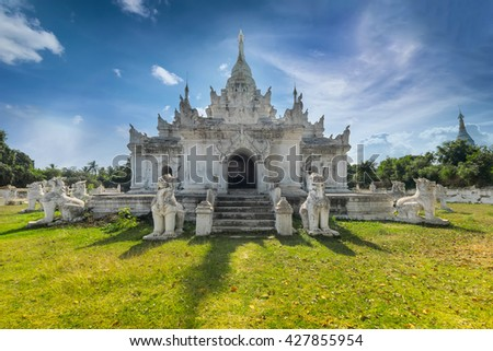 White Pagoda at Inwa ancient city with lions guardian statues. Amazing architecture of old Buddhist Temples. Myanmar (Burma) travel landscapes and destinations
