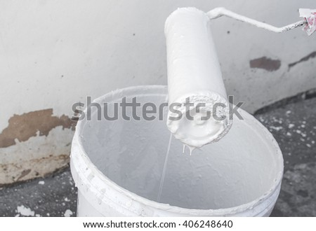 White paint dripping with paint roller, on the edge paint bucket.(select focus front  paint roller and Blur blurred background) - stock photo