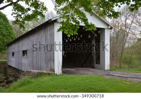 white painted covered bridge over the creek