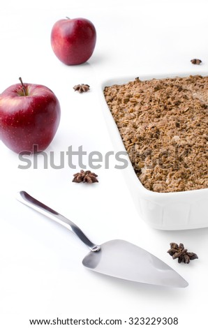 White pan with crubmle, two red apples, badian and cake server isolated on white background. - stock photo