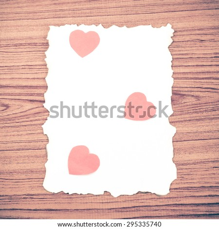 white paper and red heart on wooden background concept for valentine day vintage style - stock photo
