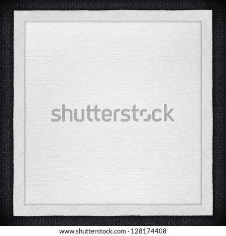 white paper background in white canvas frame on black textile texture - stock photo